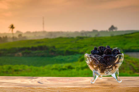 Black raisin  on old wood with a beautiful sunrise as background. Holy month of Ramadan concept. Imagens