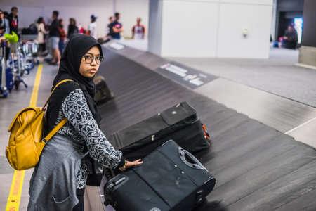 Sepang, Malaysia - Disember 21st, 2017 : Passengers collecting luggage at conveyor belt in Kuala Lumpur International Airport.