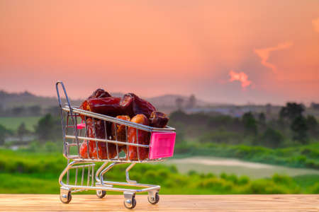 Ramadan kareem concept with dates and trolley on wooden with beautiful sunrise as background
