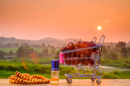 Ramadan kareem concept with dates in trolley  , rosary, and perfume on old wood with beautiful sunrise  as background Stok Fotoğraf