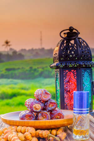 Dates fruit, perfume, lantern and rosary on old wooden table. The Muslim feast of the holy month of Ramadan
