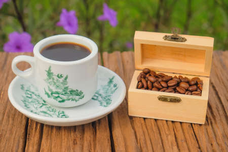 A cup of coffee using vintage  with coffee roasts in a small decorative box  on the wooden table and the plantation background with copy space for your text Imagens