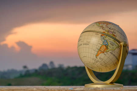 Golden globe on old wood with a beautiful sunrise as background. Travel Concept.