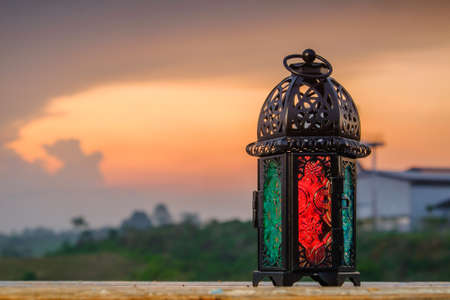 Lighting Ramadan Lantern on old wood with a beautiful sunrise as background. Holy month of Ramadan concept.