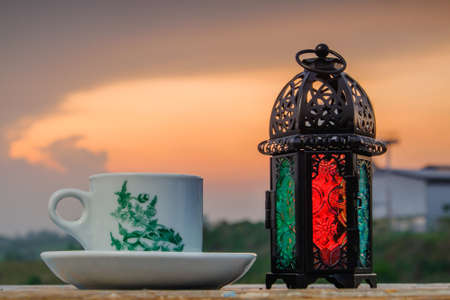 A cup of coffee using vintage cup with  lantern and sunshine in the morning. Coffee Time Concept