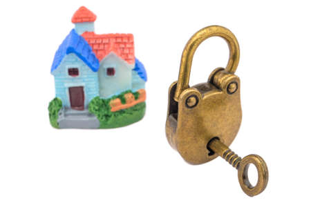 Concept of a miniature house and a golden lock with keys isolated on white background. The idea: security, protection, alarm, law and order.