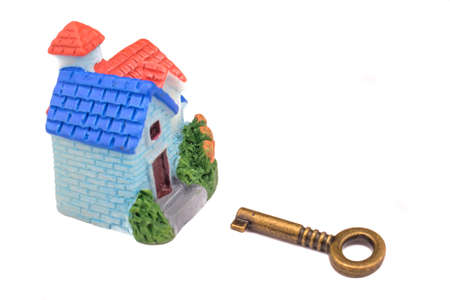Real estate concept. Miniature house and key on isolated white background . Idea for real estate concept, personal property and family house.