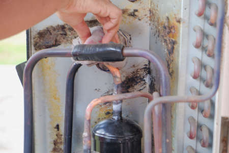 Repairman soldering copper pipe gas burner for air conditioning repair