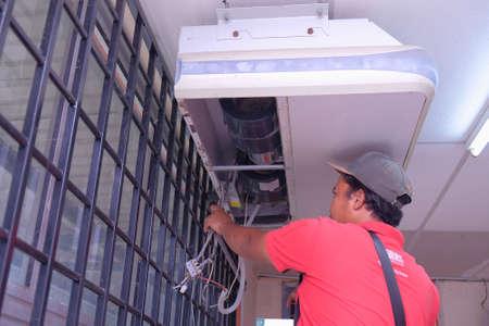Muadzam Shah, Malaysia - May 15th, 2019 : Air conditioning technician servicing 2.5Hp wall aircond in classroom At Kolej Vokasional Muadzam Shah, Malaysia.
