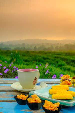 Schwarze Kaffeetasse, eine malaiische traditionelle Kekse namens Kuih Semperit, Honig-Cornflakes-Tasse, Schokoladenmandel und Florentiner Kekse auf Holztisch über unscharfem Bild der schönen Landschaft. Standard-Bild