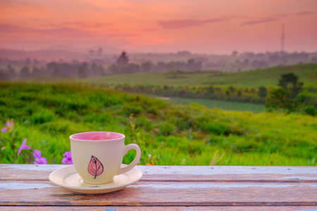 A cup of coffee on the wooden table and the beautiful sunrise  background with copy space for your text