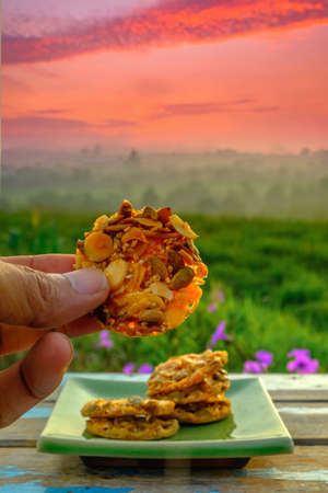 A man holding florentine cookies  on wooden table over blurred image of beautiful scenery.