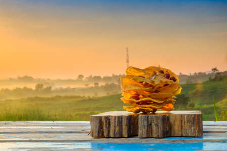 Rempeyek on wooden block during beautiful sunrise. Rempeyek Kacang or peanut crackers are fried savory Javanese crackers made from rice flour with beans by crispy flour mixture.