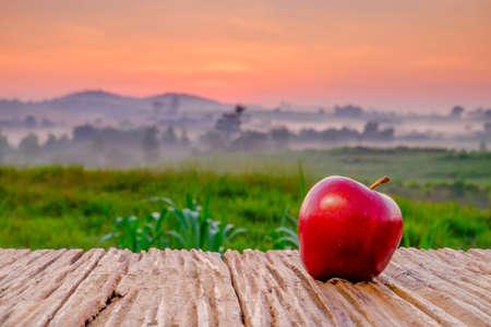 Pomme rouge sur table en bois le matin au lever du soleil avec ferme verte et beau lever de soleil