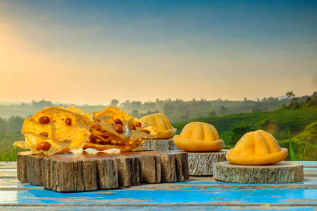 Malaysia traditional sweet as known as Baulu or Bahulu and Rempeyek on wooden block during beautiful sunrise.