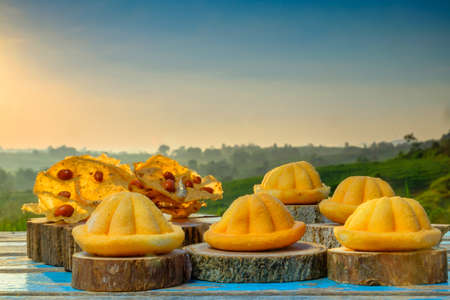 Malaysia traditional sweet as known as Baulu or Bahulu and Rempeyek on wooden block during beautiful sunrise. Imagens