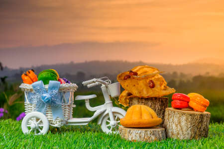 Malaysia traditional sweet as known as Baulu or Bahulu and Rempeyek with Macaron on wooden sliced during beautiful sunrise.