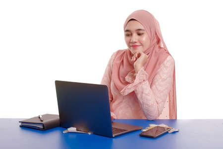 Jolie jeune femme portant le hijab devant la recherche d'un ordinateur portable et faisant du travail de bureau avec une expression de visage différente isolée sur fond blanc - concept de bureau, d'affaires, de finance et de poste de travail.