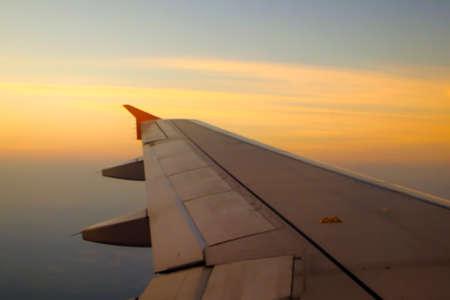 Fliegen und reisen, Blick aus dem Flugzeugfenster auf dem Flügel bei Sonnenuntergang Standard-Bild