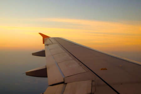Flying and traveling, view from airplane window on the wing on sunset time Banco de Imagens