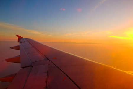 Fliegen und reisen, Blick aus dem Flugzeugfenster auf dem Flügel bei Sonnenuntergang