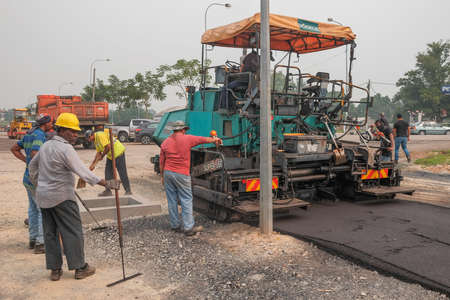 Ayer Hitam, Malaysia - September 22nd , 2019 : Workers making asphalt with shovels at road construction Editorial