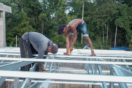 Muadzam Shah, Malaysia - October 8th, 2019 : Construction workers installing metal roof trusses at the construction site.