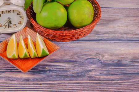 Citrus fruits and alarm clock with green leaves isolated on wood background