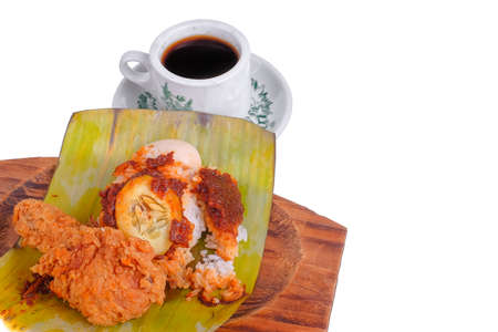 Nasi Lemak or Spicy Rice . Nasi lemak is a traditional Malay rice cooked in coconut milk with pandan leaf .  Wrapped in banana leaf with spicy chili sambal,fried anchovies,egg.cucumber slice and peanut Stock Photo - 133129191