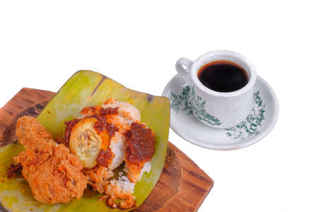 Nasi Lemak or Spicy Rice . Nasi lemak is a traditional Malay rice cooked in coconut milk with pandan leaf .  Wrapped in banana leaf with spicy chili sambal,fried anchovies,egg.cucumber slice and peanut Stock Photo - 133129193