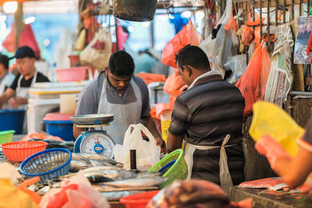 Kuala Lumpur, Malaysia - December 2nd, 2019 :  A wet market selling different colorful fishes with people buying in the morning .