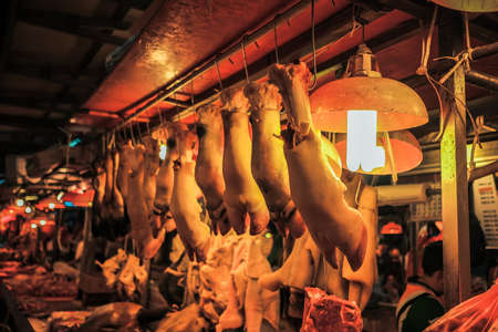 Kuala Lumpur, Malaysia - December 2nd, 2019 :  Malaysian male butchers sell chopped beef meat on the counter at the wet market in the morning .