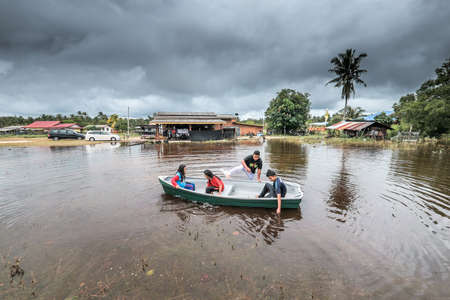 Rompin, Malaysia- December 16th, 2019 : A group of kids playing fiber boat on a flood water in front of the house.