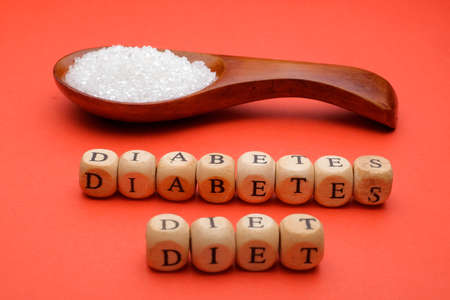 Health concept. Sugar in a wooden spoon with a DIABETES  DIET wording on red background