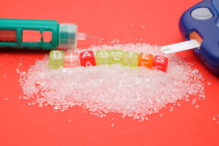 Health concept. Sugar with a DIABETES wording , glucometer and insulin on red background