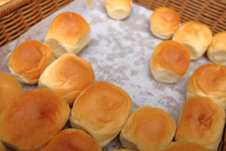 Lots of fresh bread in a basket on a table
