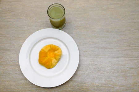 Guava juice in glass and fresh bread on the white plate served on a table