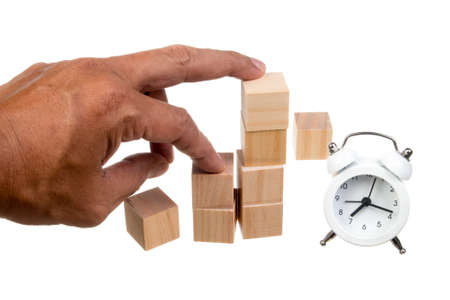 Hand holding blank wooden cubes with  white alarm clock . Business concept background, mock up, template
