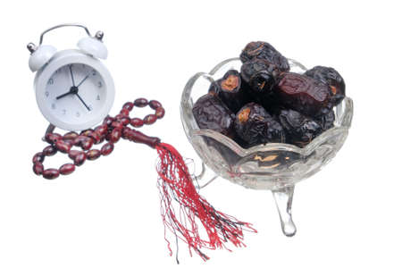 Dried dates fruits on a plate, honey, alarm clock, and prayer beads or tasbih isolated on white background. Fasting month Ramadhan concept.