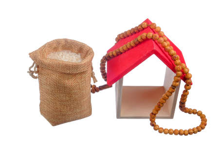 """Rice in the sack, rosary and mini house isolated on white background. Muslim concept for zakat property, income and """"Fitrah"""" zakat."""
