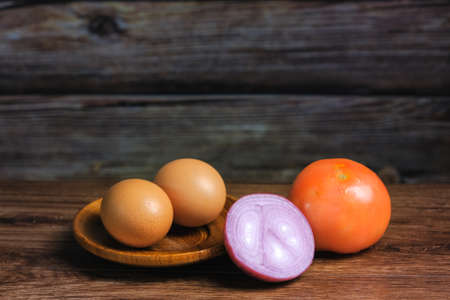 Egg. tomato  and onion  on a wooden background. The concept of cooking.