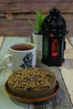Traditional cookies in Malaysia during Hari Raya Festival known as Kuih Kole Kacang with lantern and tea  on the wooden background