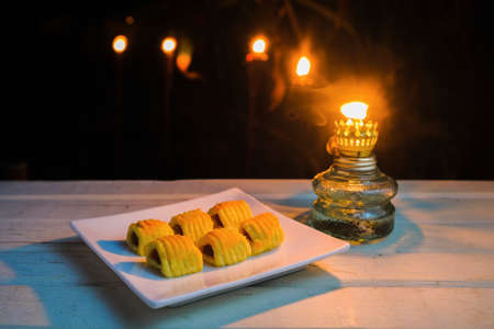 Closeup of traditional snack during Hari Raya Aidilfitri in Malaysia called kuih tart or pineapple tart with vintage oil lamp at night.