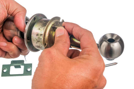 The closeup of worker hands assembling door knob isolated on white background. Reklamní fotografie