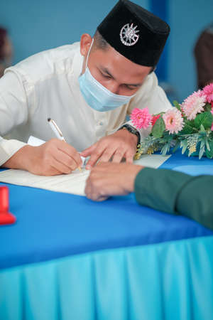 A muslim couple getting solemnization in medical face masks during coronavirus pandemic. COVID-19 weddings. Social Distancing. Stay Safe