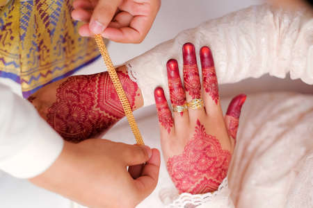 The groom put the wedding bracelet to the bride during solemnization ceremony. Family and happiness concept