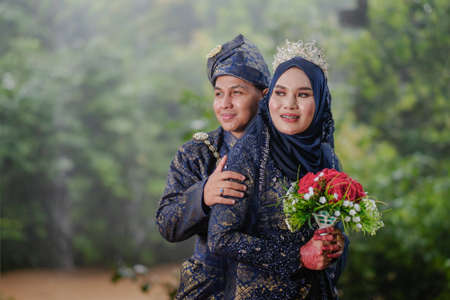 Creative outdoor photo shoot with lighting of a Malay loving couple bride and groom on their wedding wearing a traditional Malay dress