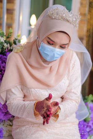 A muslim couple pose  in medical face masks during coronavirus pandemic. COVID-19 weddings. Stay Safe  . Stock Photo - 150783526