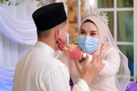 A muslim couple pose  in medical face masks during coronavirus pandemic. COVID-19 weddings. Stay Safe  . Stock Photo - 151537746