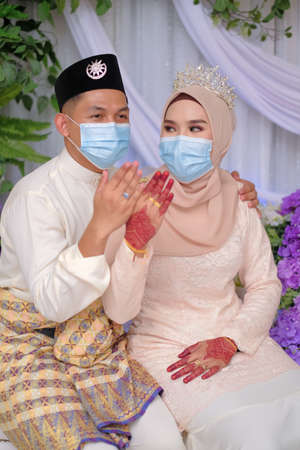 A muslim couple pose  in medical face masks during coronavirus pandemic. COVID-19 weddings. Stay Safe  . Stock Photo - 151537753